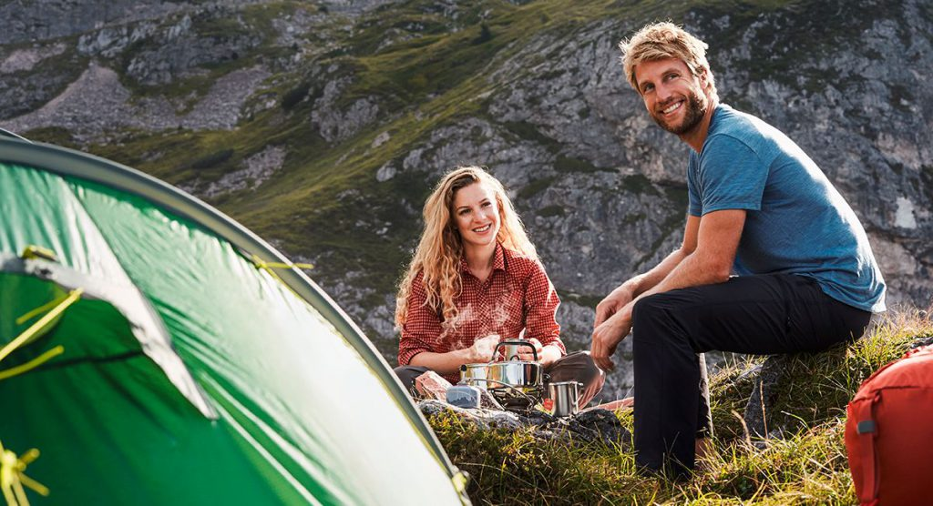 A woman and a man on a trekking tour sitting next to a tent.