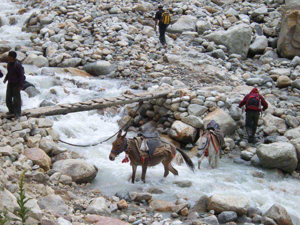 Indien Trekking - Pilger und Trekker beim Überqueren eines Flusses.