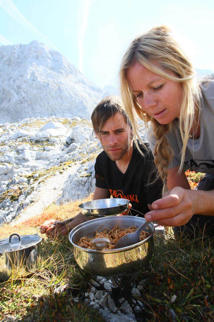Trekking-Nahrung - Mann und Frau in den Bergen beim Nudeln kochen.