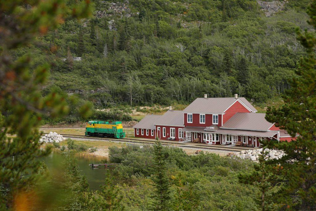 Blick auf das Bahnhofsgebäude aus Holz mit grüner Eisenbahn.