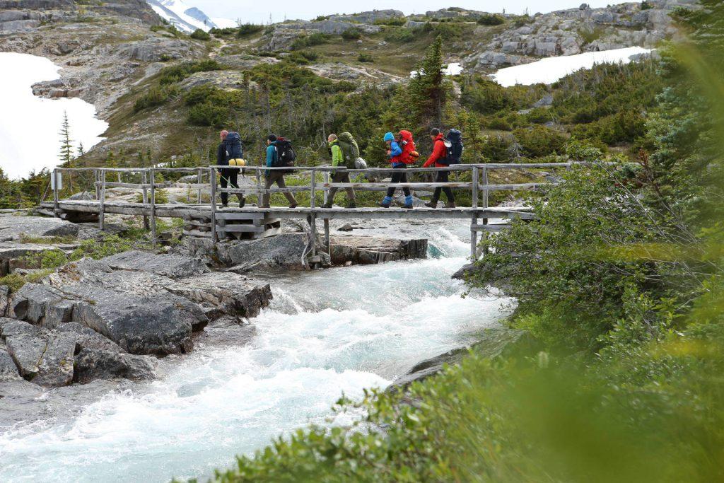 Trekkingtour Chilkoot Trail - Trekker laufen über eine Brücke im Yukon Territorium.