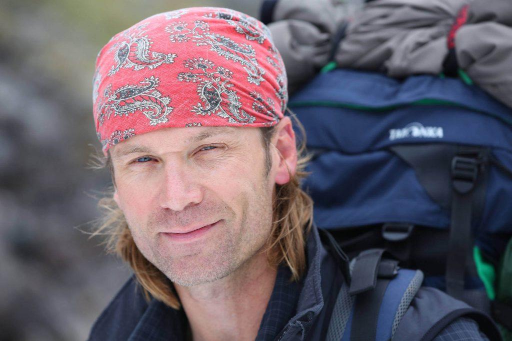 Porträtfoto von Dirk Rohrbach mit rotem Kopftuch und Tatonka Rucksack auf dem Rücken.
