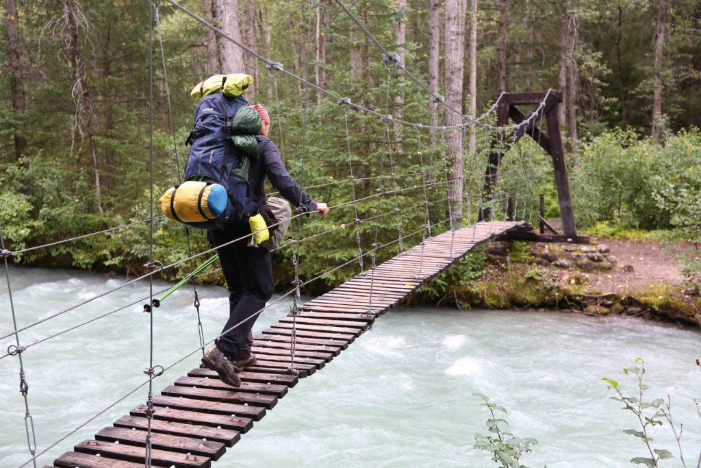 Dirk Rohrbach mit Trekkingrucksack beim Überqueren einer Hängebrücke auf dem Chilkoot Trail.