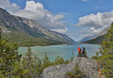 Zwei Trekker mit Trekkingrucksäcken blicken von einem Plateau auf den Yukon River.