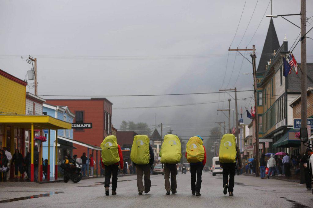Trekkingtour Chilkoot Trail - Fünf Trekker laufen mit ihren Rucksäcken durch die Stadt Skagway.