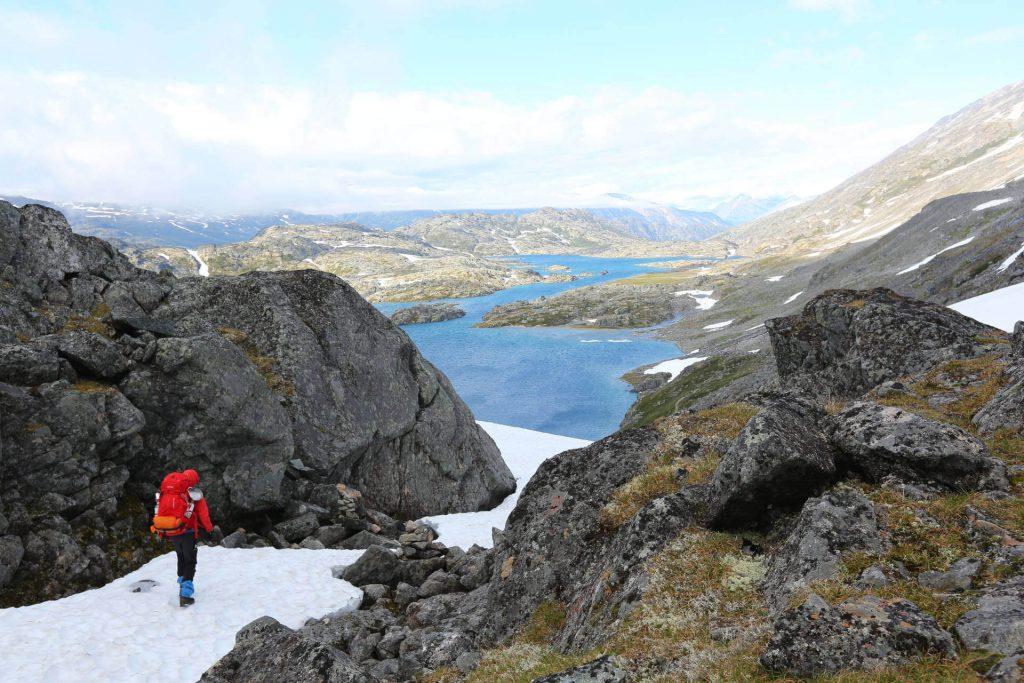 Ein Trekker wandert in den Bergen auf Schnee und blickt auf den Yukon River.