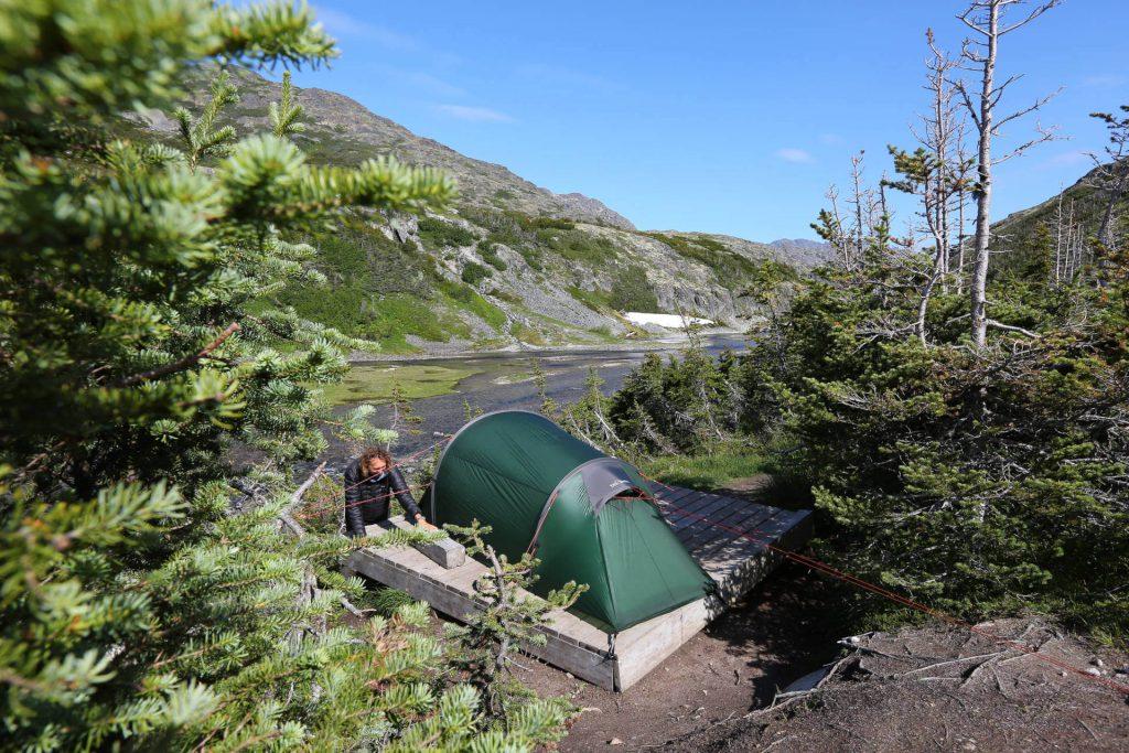 Ein Teilnehmer baut das Tatonka Kiruna Tunnelzelt auf einer Holzplattform nahe des Flusses auf.