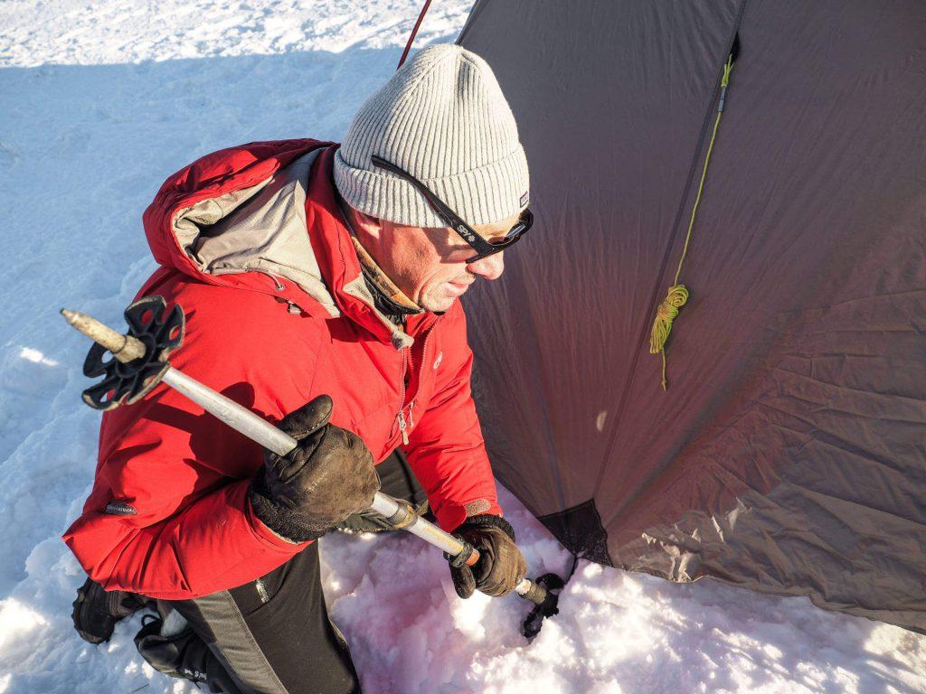 Michael Bösiger nimmt einen Skistock zum Abspannen seines Zeltes zur Hilfe.