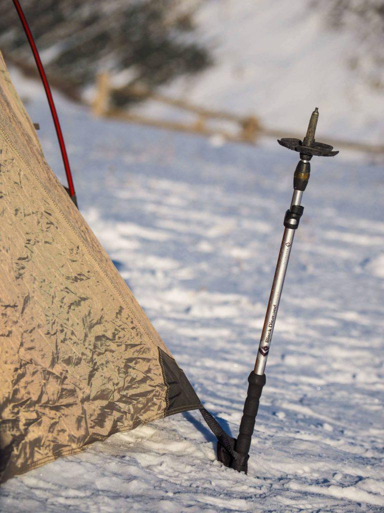 Ein Skistock dient als Hilfe beim Abspannen der Zeltleine.
