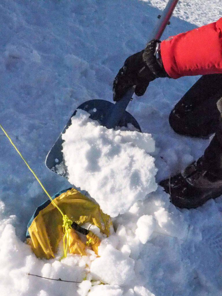 Befüllter Packsack wird in den Schnee eingegraben.