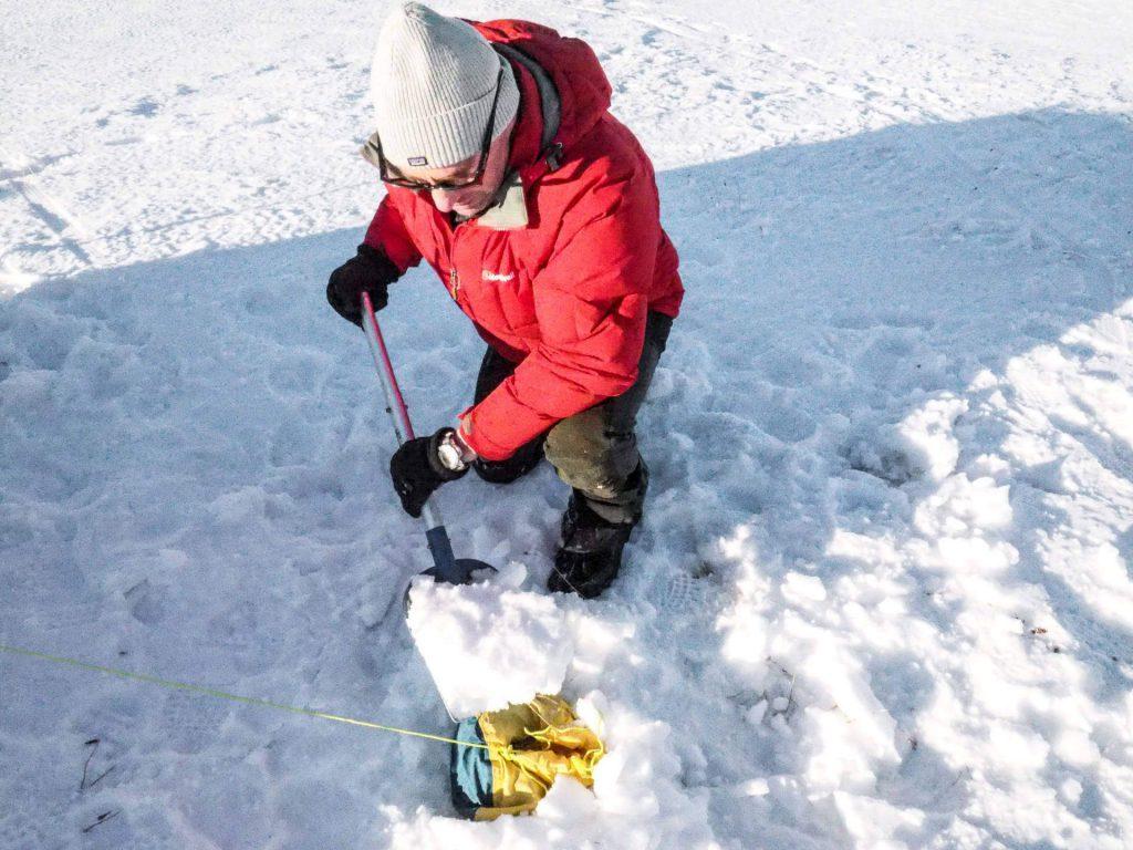 Michael Bösiger bedeckt einen Packsack mit Schnee, der als Abspannhilfe für das Zelt beim Wintercamping dient.