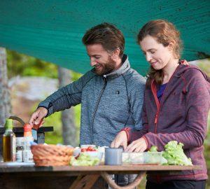 Zwei Menschen kochen ein Essen beim Zelten.