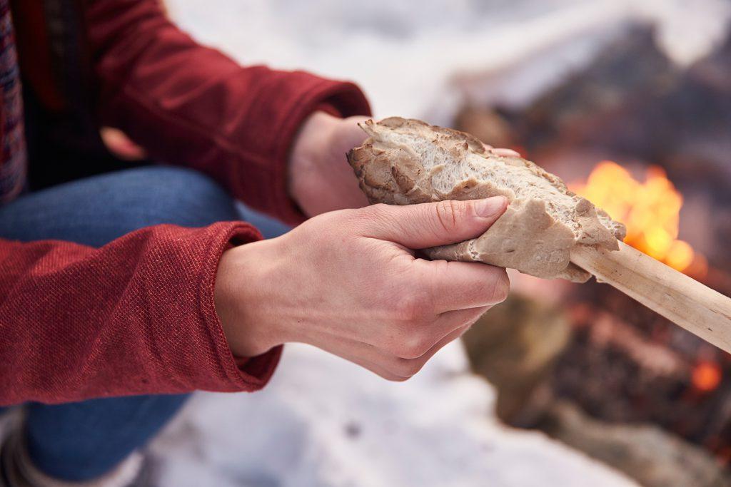 Camping-Küche: Frau hält Stockbrot in den Händen neben einem Lagerfeuer