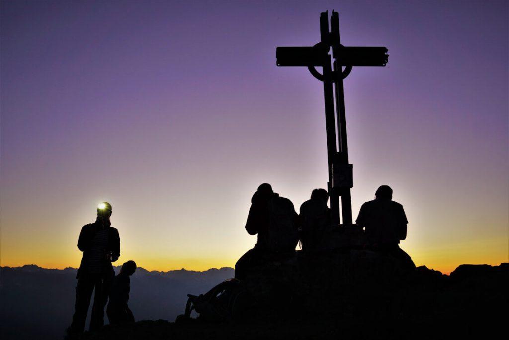 Warten auf den Sonnenaufgang am Gipfelkreuz der Pfriemeswand in Innsbruck.
