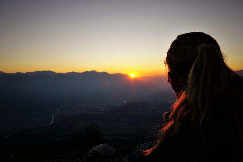 Karin genießt den Sonnenaufgang auf der Pfriemeswand bei Innsbruck.