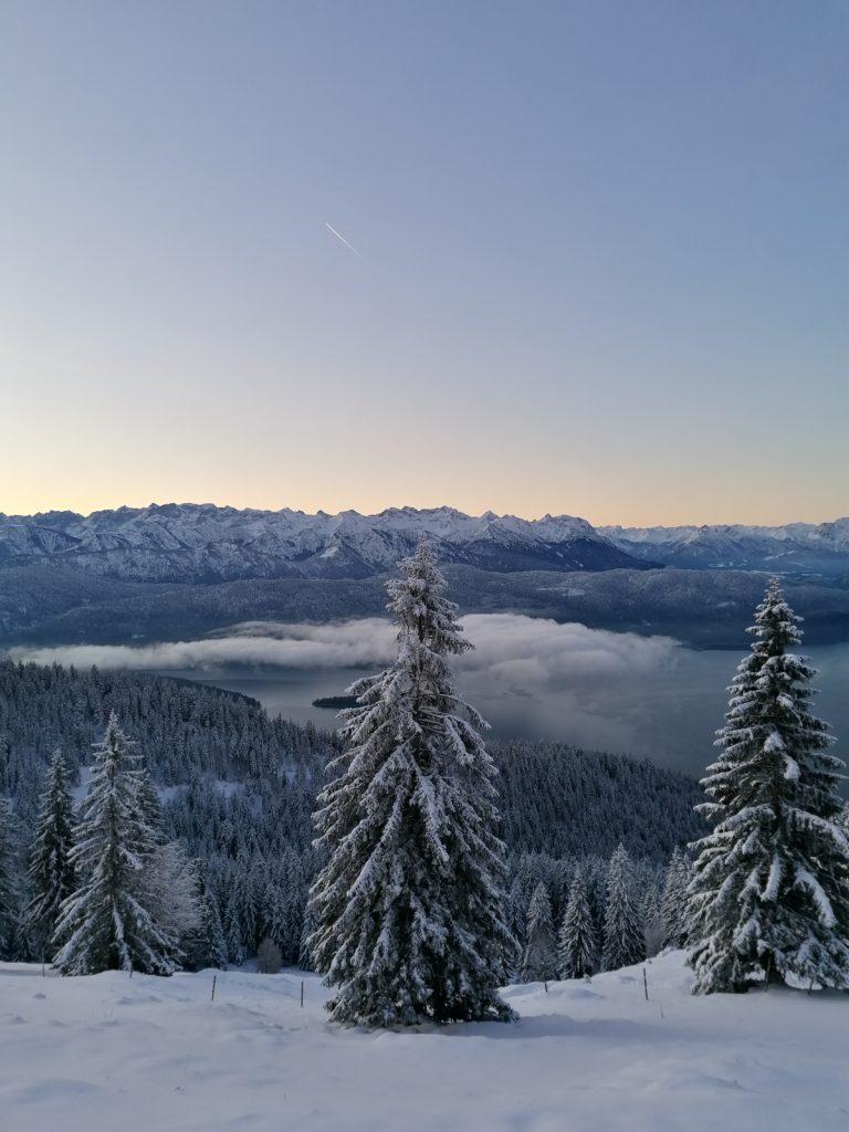 Nebel liegt frühmorgens über dem Walchensee.