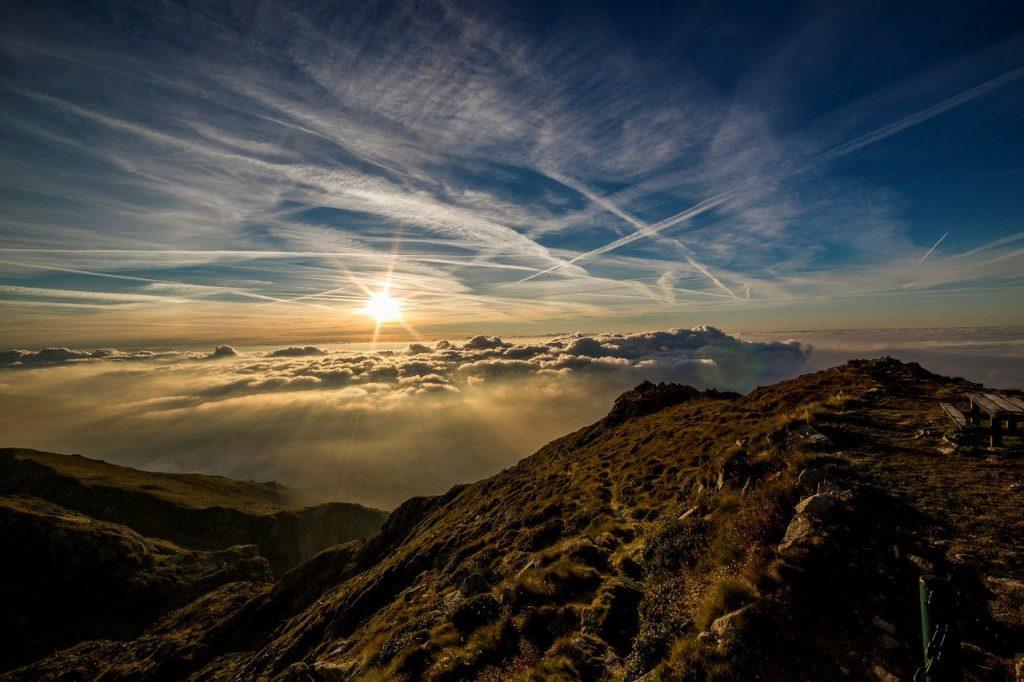 Kondensstreifen am Himmel über den Bergen helfen bei der Bestimmung des Wetters.
