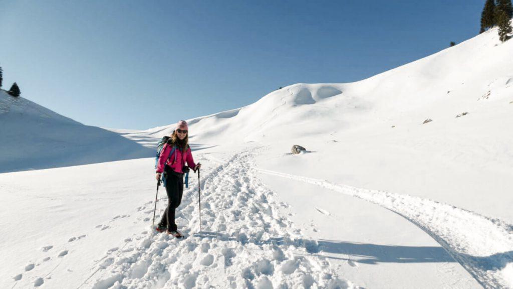 Mit Stöcken und Grödeln über schneebedeckte Wanderwege.